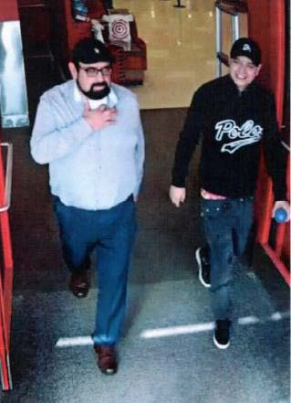 2 men shown exiting target. Man on left has a beard and dressed in black baseball cap, glasses, light blue dress shirt, jeans and dress shoes. Man on right dressed in black baseball cap, black sweater and jeans with black tennis shoes.