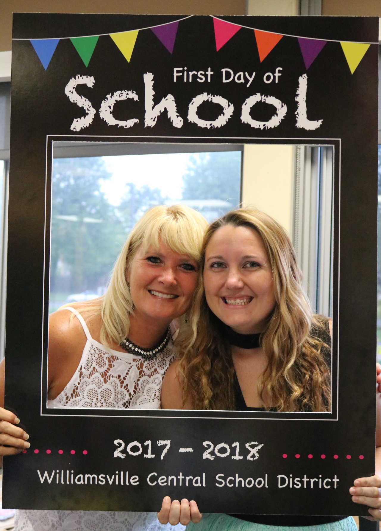 Middle school office staff hold up photo frame